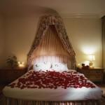 Разхвърляните розови листенца по леглото помагат за романтичната атмосфера на Свети Валентин