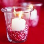 Свещ, поставена в чаша на подложка от цветен пясък